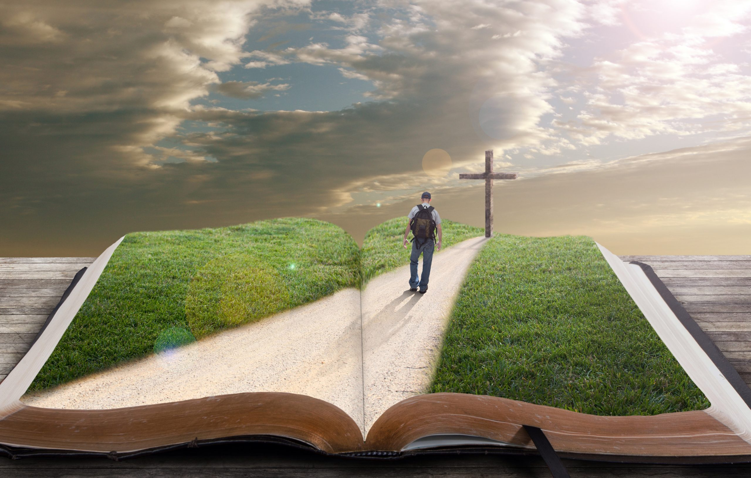 An open bible with grass and a man walking towards a cross